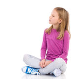 Little girl sitting with legs crossed Royalty Free Stock Images
