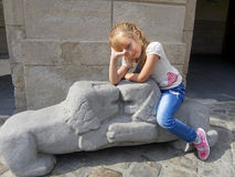 Little girl sitting on the lions sculpture Stock Images