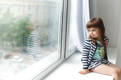Little girl sitting and looking to the window. Portrait of a little girl sitting on a windowsill and looking to the window Royalty Free Stock Images