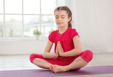 Little girl sitting in lotus position with closed eyes Stock Photo