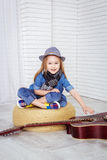 Little girl sitting in the lotus position and holding a guitar Royalty Free Stock Photo