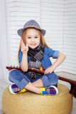 Little girl sitting in the lotus position and holding a guitar royalty free stock image