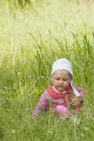 Little girl sitting on meadow Stock Photography