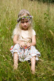 Little girl sitting at the meadow stock photos