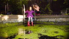 Little girl sitting on a metal ladder and dangling feet in the old pool overgrown with duckweed. Crane shot. Little girl sitting on a metal ladder and dangling stock video