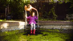 Little girl sitting on a metal ladder and dangling feet in the old pool. Overgrown with duckweed stock images