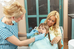 Little girl sitting in mom's lap while dentist examines her teet Royalty Free Stock Images
