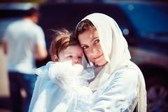 Little girl sitting on mother`s hands. Adorable little girl sitting on hands of mother looking at camera outdoors royalty free stock photo