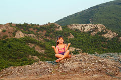 Little girl sitting on a mountain top Royalty Free Stock Image