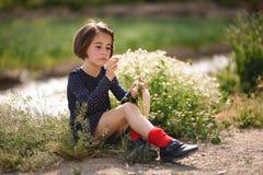 Little girl sitting in nature field wearing beautiful dress Stock Image