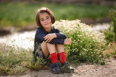 Little girl sitting in nature field wearing beautiful dress Royalty Free Stock Photo
