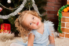 Little girl sitting near Christmas tree Stock Photography