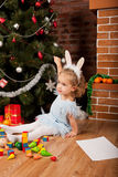 Little girl sitting near Christmas tree Stock Images
