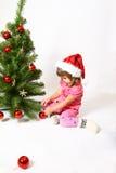 Little girl sitting near Christmas tree  Royalty Free Stock Photography