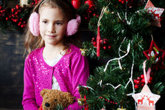 Little girl sitting near the a Christmas tree Stock Images