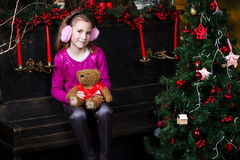 Little girl sitting near the a Christmas tree Stock Photo