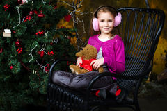Little girl sitting near the a Christmas tree Royalty Free Stock Photos