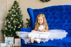 Little girl sitting near the Christmas tree with a New Year`s gift stock images