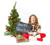 Little girl sitting near a Christmas tree with a sign with the w Royalty Free Stock Image