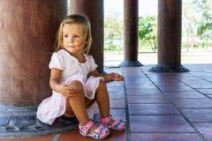 Little girl sitting near the column Royalty Free Stock Image