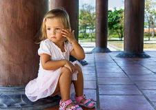 Little girl sitting near the column royalty free stock photography