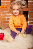 Little girl sitting near fireplace Stock Photography