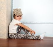 Little girl is sitting near fireplace Royalty Free Stock Image
