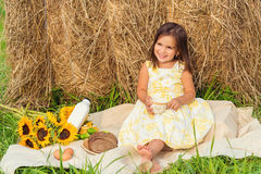 Little girl sitting near haystack having a picnic (Annapolis Val Royalty Free Stock Image