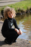 Little girl sitting near a lake Stock Images