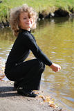 Little girl sitting near a lake Stock Photography