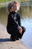 Little girl sitting near a lake Royalty Free Stock Image