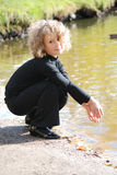 Little girl sitting near a lake Royalty Free Stock Photos