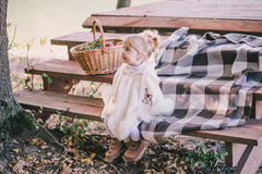 Little girl sitting near lake in autumn fores. Little girl wearing poncho sitting near lake in autumn forest Stock Photo