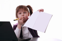 A little girl is sitting near the notebook Royalty Free Stock Images