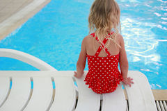 Little girl sitting near the pool Royalty Free Stock Images
