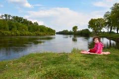 Little girl sitting near the river. Stock Photos