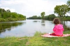 Little girl sitting near the river. Stock Images