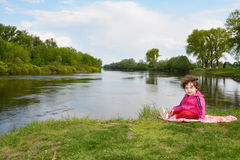 Little girl sitting near the river. Stock Photos