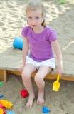 Little girl sitting near sandbox Royalty Free Stock Photos