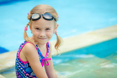 Little girl sitting near swimming pool Stock Photo