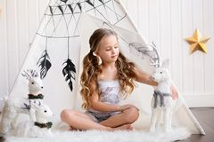 The little girl is sitting near the wigwam. royalty free stock photo