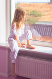 Little girl sitting near the window Royalty Free Stock Photography