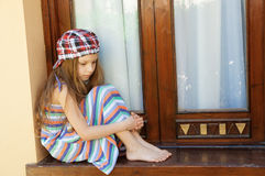 Little girl sitting near window Royalty Free Stock Photo