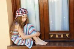 Little girl sitting near window Royalty Free Stock Photo