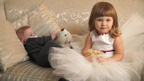 Little girl sitting next to the little brother on the couch stock footage