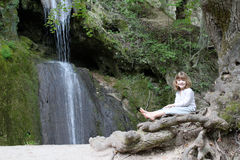 Little girl sitting next to a waterfall Royalty Free Stock Images