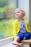 Little girl sitting next window on rainy day Royalty Free Stock Photo