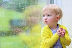 Little girl sitting next window on rainy day Royalty Free Stock Image