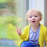 Little girl sitting next window on rainy day Stock Photos