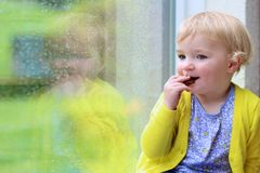 Little girl sitting next window on rainy day Stock Images